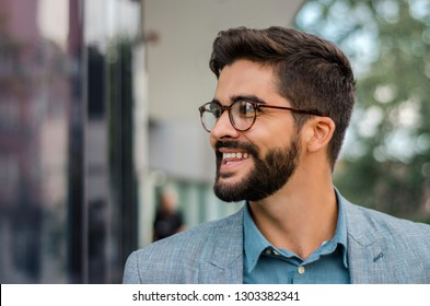 Closeup outdoors portrait of handsome dark hair bearded man with stylish eyeglasses