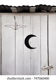 closeup of outhouse door with crescent moon cutout