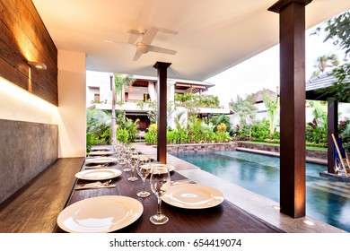 Closeup of an outside dining area, including wooden tables and white plates beside wine glasses near to the pool and the house