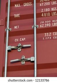 Close-up of outside of red shipping container with handles and standard weight information printed on the outside