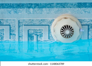 Closeup of an overflow drain outlet mechanism set in a swimming pool with water. Copy space.