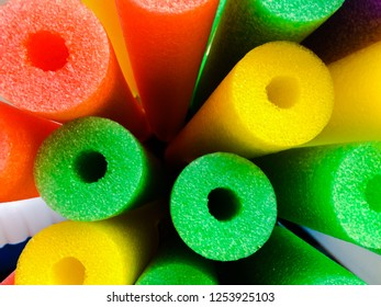 Closeup overhead view of colorful pool noodles in orange, yellow, green and purple