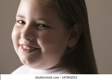 Closeup of an overweight girl smiling against gray background