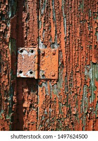 closeup of oxide orange pealing paint on grainy wood surface historic building romania
