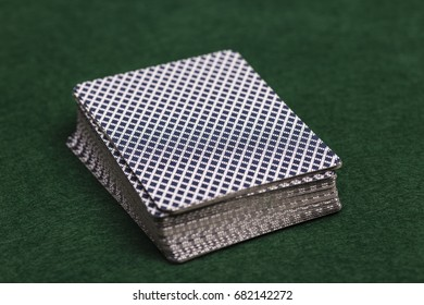 Close-up of a pack of playing-cards face down on a green baize cloth