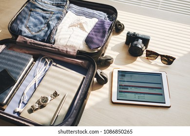 Close-up of packed suitcase for a new journey and touchpad with electronic ticket on the table