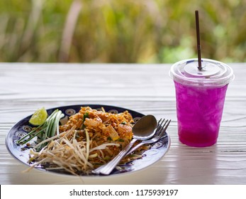 Close-up of padthai (Thai Food) and Herb water on white wooden table.