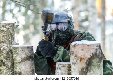Closeup of paintball player shooting from the wooden fortification