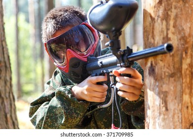 Close-up of paintball shooter in mask outdoors