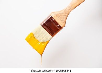 Close-up paintbrush with liquid yellow paint drips off the brush
