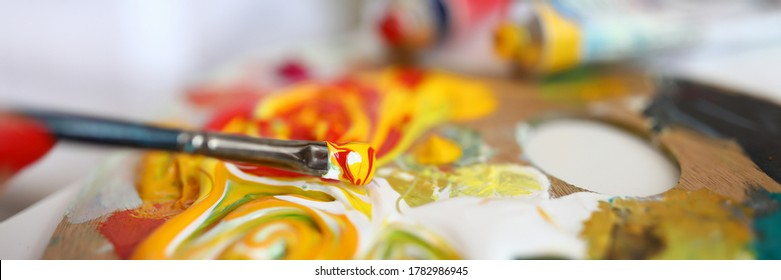 Close-up of paintbrush with mixed yellow and red paints. Creamy oil paints on palette. Painter equipment for work. Masterpiece idea. Creativity flow. Artistry concept