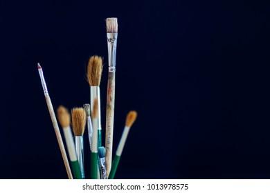 Closeup of paintbrushes isolated on blue background