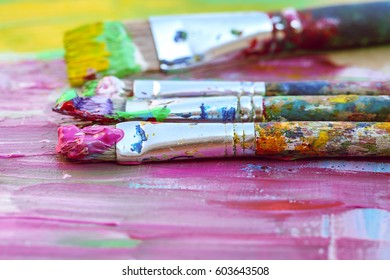 Closeup of paintbrushes on colourful background