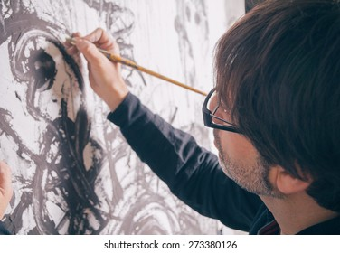 Closeup of painter artist working in a modern abstract oil canvas in his studio