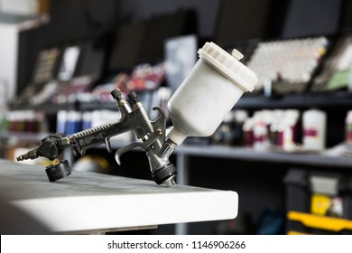 Closeup of paint-spray gun on table in professional car painting workshop