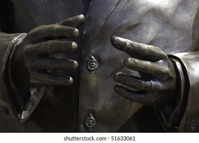 Closeup of a pair of bronze hands gesturing assistance