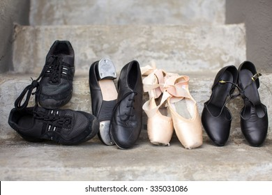 Closeup of a pair of jazz shoes, tap shoes, ballet pointe shoes, and character shoes representing a variety of dance classes in one image. Shoes are resting on concrete steps.