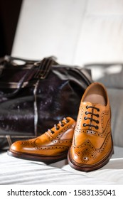 Closeup of Pair of Male Full Brogued Tan Oxford Shoes Placed With leather Men's Bag On Pale Sofa Indoors. Vertical Shot