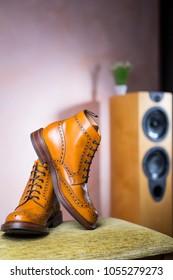 Closeup of Pair of Mens Tanned Semi-Brogue Boots on One Another Indoors. Against of Floorstanding Loudspeaker on Background.Vertical image Composition