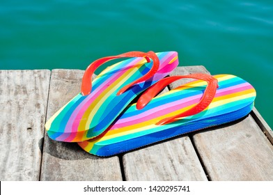 closeup of a pair of rainbow-patterned flip-flops on a weathered dock, next to the ocean or a pond