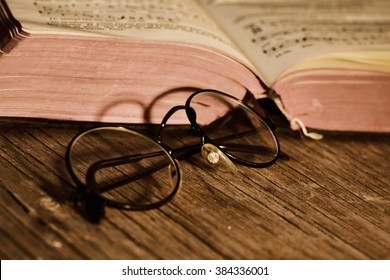 closeup of a pair of retro round-framed eyeglasses and an open old book on a rustic wooden table, with a filter effect