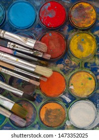 Close-up of a palette with watercolors and many brushes
