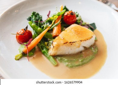 Close-up Pan seared Cod fish fillet with tomato, bean and carrot in gravy sauce. Served in a white plate with a silver knife and fork.