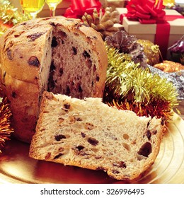 closeup of a panettone, a typical Italian sweet for Christmas time, in a golden tray on a table with some glasses with champagne and gifts