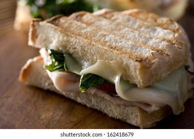 Closeup of a panini sandwich with turkey, melted cheese, tomato and spinach.