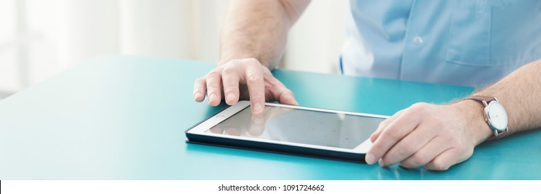 Close-up panorama of a male doctor's hands on a table, checking medical history information of a patient on a tablet