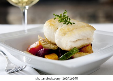 Closeup of pan-seared halibut on a bed of roasted vegetables.