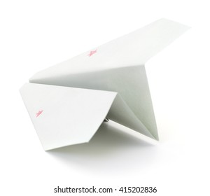 Closeup of a paper airplane on white background.