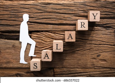 Closeup of paper businessman climbing salary block ladder on wood