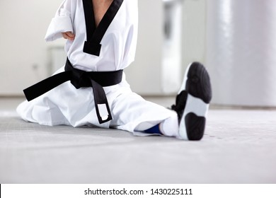 Close-up of a para-athlete doing leg splits dressed in white