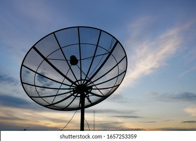 Close-up parabolic satellite dish with clouds in in sunset background