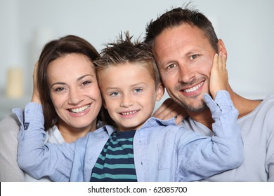 Closeup of parents and child relaxing at home on sofa