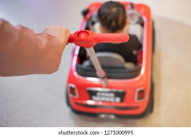 Close-up of parent's hand pushing big car toy for child