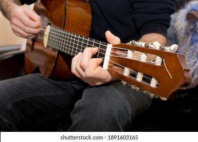 Close-up of part of man dressed in black Jeans and blue pullover with fingers of left hand on fingerboard playing the acoustic guitar