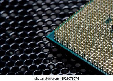 Close-up of a part of a microprocessor in soft focus under high magnification. Dark background with detail of a computer component under a microscope
