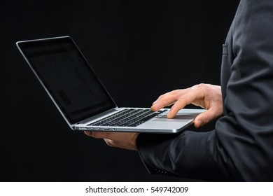 Close-up partial view of businessman using laptop isolated on black