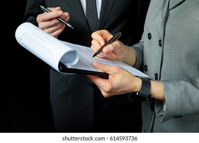 Close-up partial view of businesspeople discussing and signing papers   isolated on black