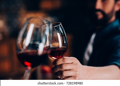 close-up partial view of friends clinking glasses of red wine