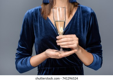 close-up partial view of gorgeous woman holding glass of champagne isolated on grey