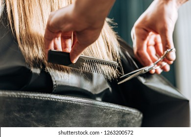 close-up partial view of hairstylist cutting hair to beautiful young woman in beauty salon
