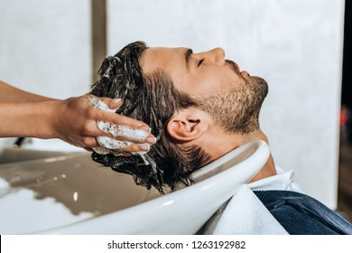close-up partial view of hairstylist washing hair to handsome young man in beauty salon