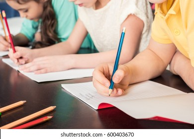 Close-up partial view of schoolchildren writing with pencils
