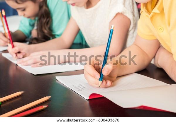 Gros plan sur une vue partielle d'écoliers écrivant avec des crayons