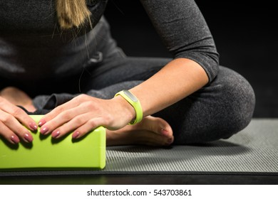 Close-up partial view of sportswoman exercising with yoga block isolated on black
