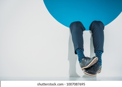 close-up partial view of stylish man falling into hole on grey