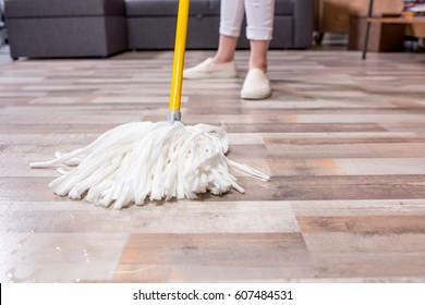 Close-up partial view of woman cleaning floor with mop
